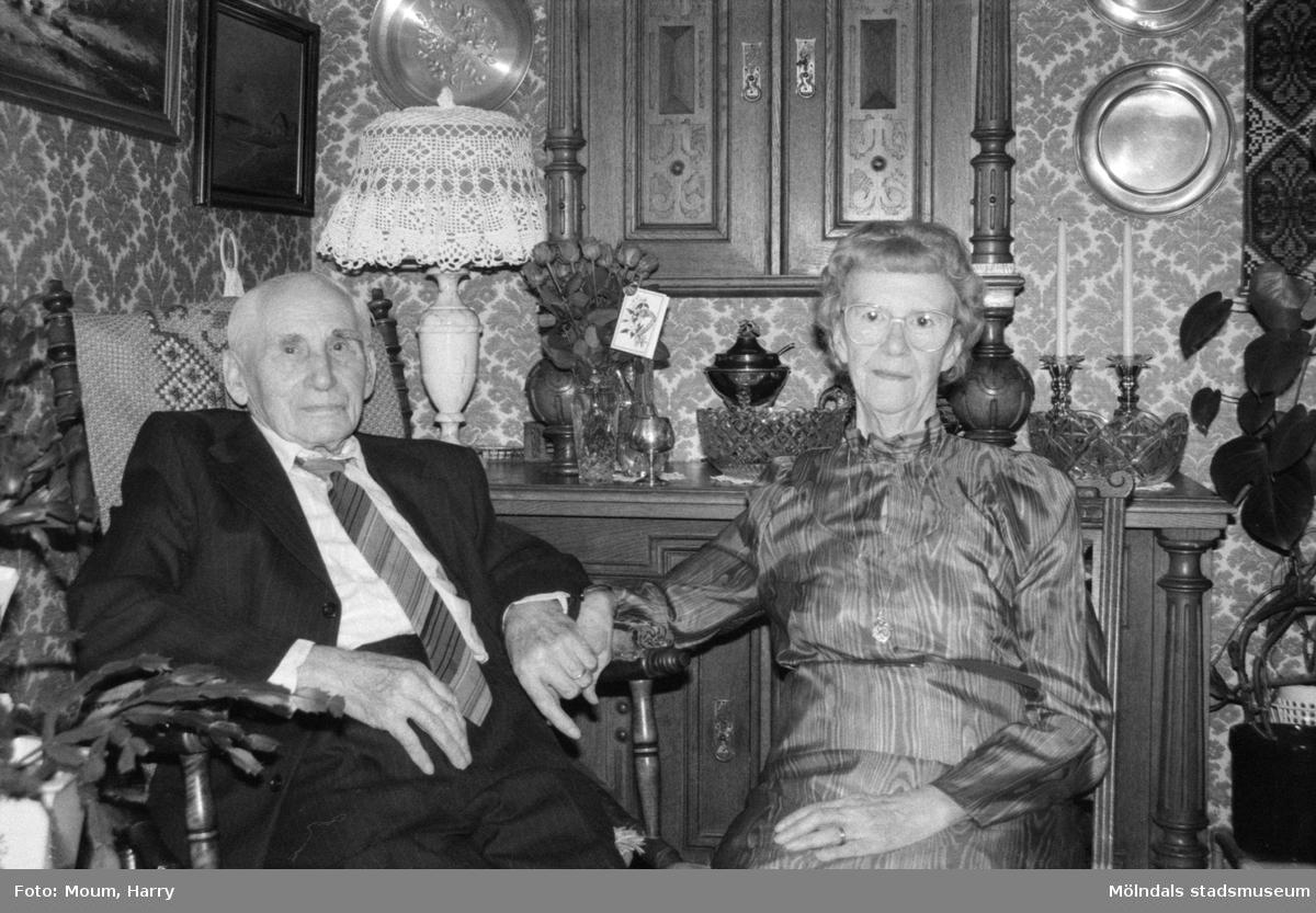 """Ester och Ture Larsson firar 60-års bröllopsdag i Humlekärr, Lindome, år 1984. """"Ester och Ture på sin stora dag. Medaljongen från honom, blommor och silverbägare från henne finns på plats.""""  För mer information om bilden se under tilläggsinformation."""