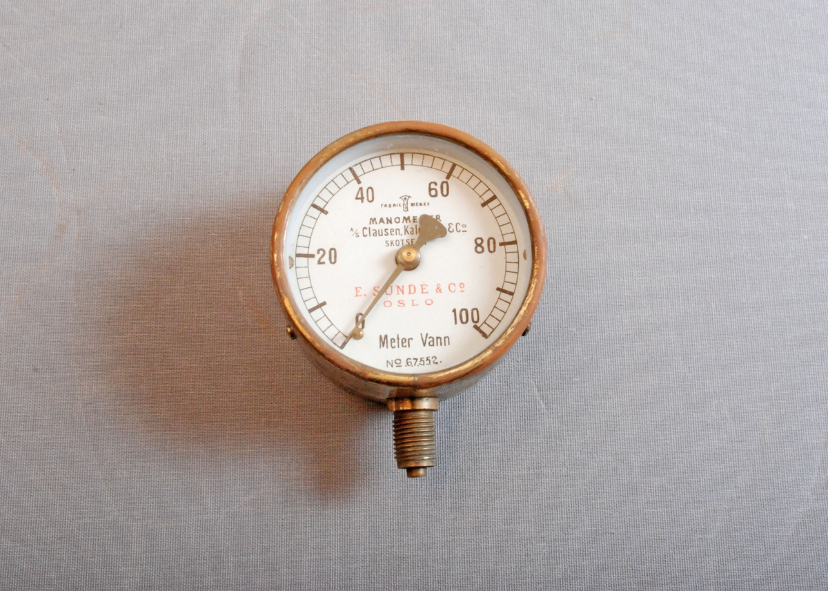 Manometer for trykkmåling av vannstråle. Rundt manometer for feste på messingkran. Måleskala fra 0-100.