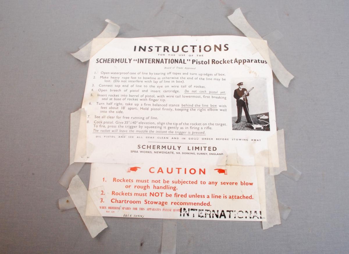Bruksanvisning trykket og limt til innsiden av lokket på kofferten for oppbevaring av linepistolen. Instruksjonen er i to deler satt sammen med tape. Påtrykt tekst og bilde i svart, hvitt og rødt