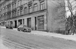 bygård, radioforretning, utstillingsvindu, bakeriutsalg, E.K. Egner kolonial- og kjøttforretning, motorsykkel, sidevogn, bil, Aero Minor, snø