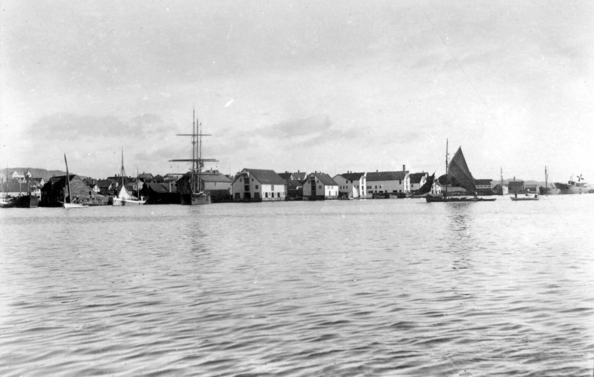 Risøy sett fra vest. Kortanes til venstre. Sjøhusbebyggelse med seilskuter og mindre båter fortøyd ved.