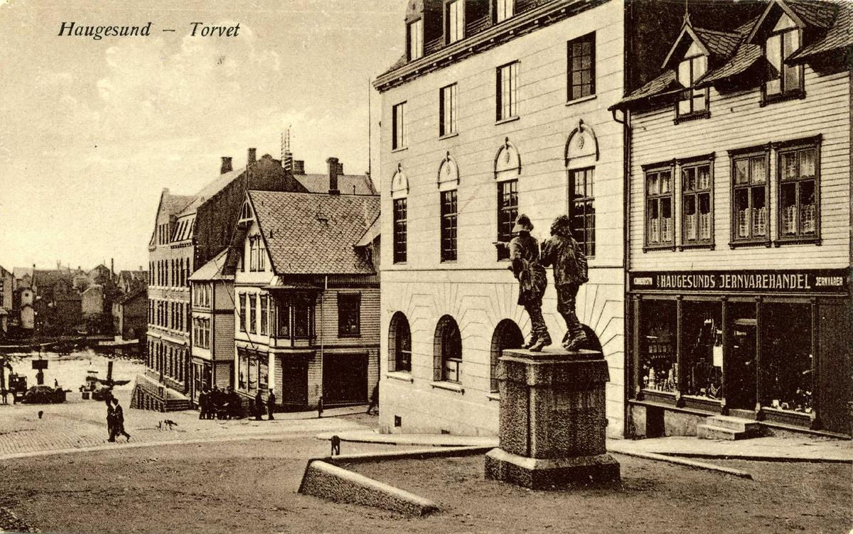 """Torggaten med """"Fiskerne"""" og Strandgaten nedenfor.Langs bakken vekselvis tre- og murbygninger. På huset til h. et skilt med """"Haugesunds jernvarehandel""""."""