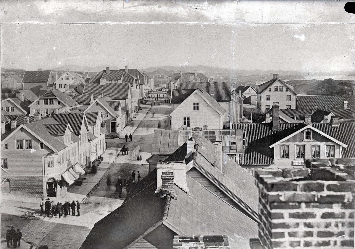 Strandgt. sett fra nord (mot sør). Huset helt til v. er Torggt. 7. Huset til h., nedenfor Strandgt., med skilt for fotograf, er Torggt. 3. Peder Amlie jr.,  en av byens første fotografer hadde fotografatelier her fra ca. 1885.