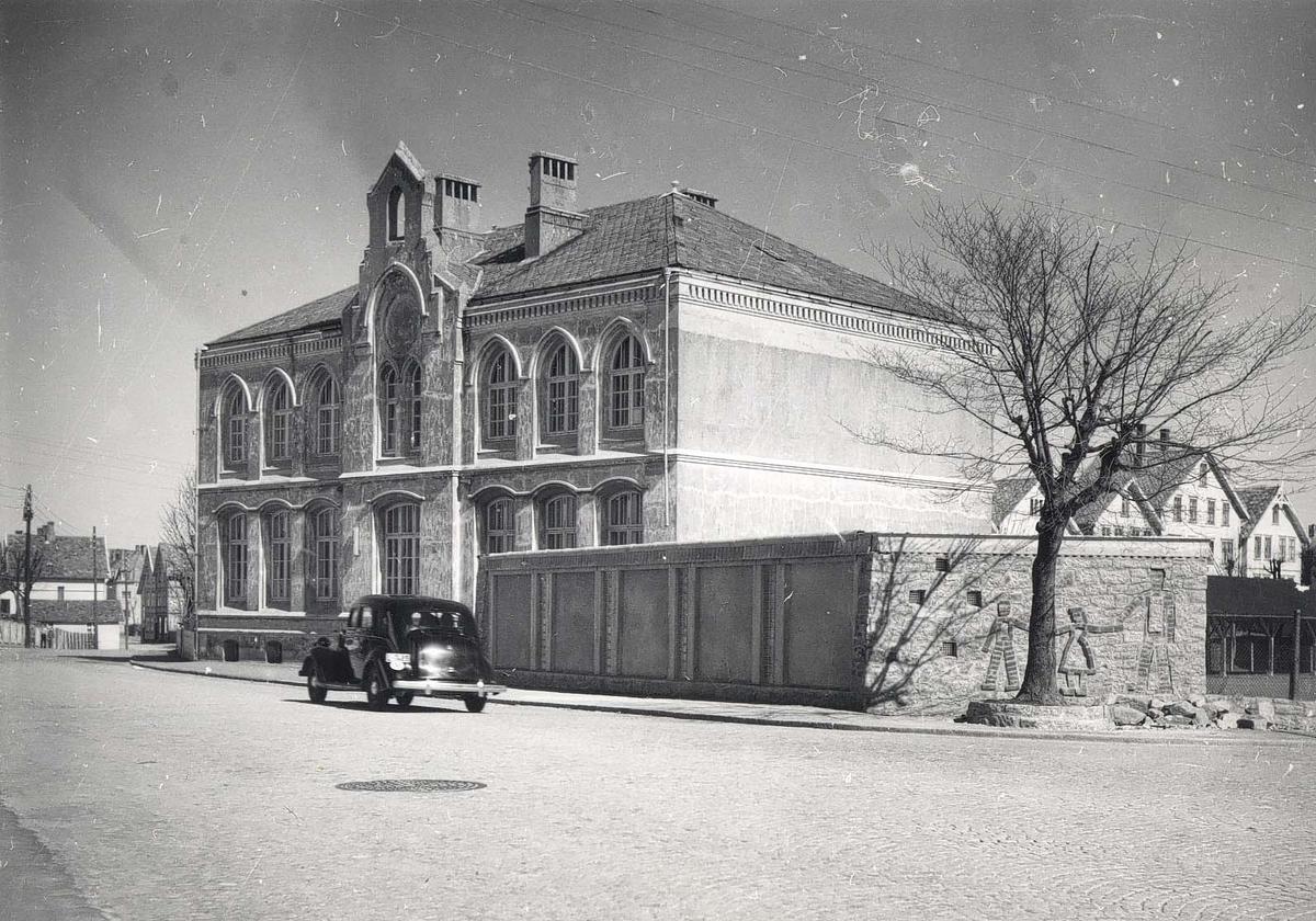 Haugeveien med Hauge skole. Svart bil passerer fasaden