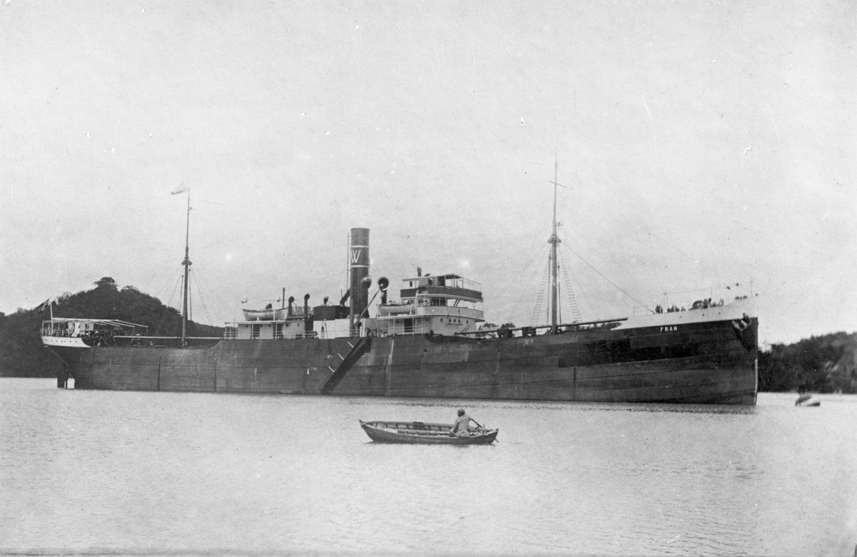 """Dampskipet D/S """"Fram"""" ankret opp ved en kyst. I forgrunnen ror en mann en liten trebåt."""