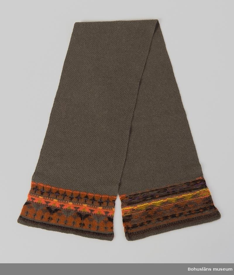 Stickad halsduk i ullgarn. Mönstret Senhöst i de två ändarna. Mosstickad mellandel i mellangrått garn.