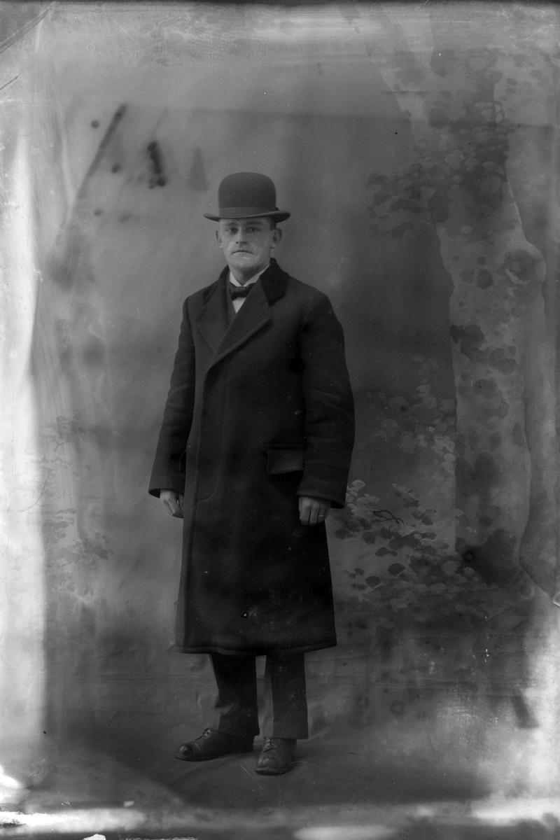 Studioportrett av en mann med hatt på hodet.