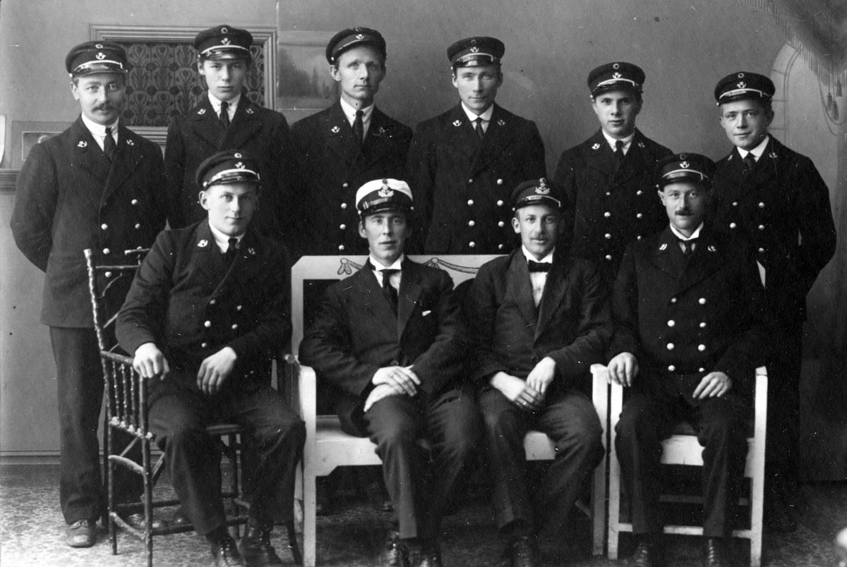 Gruppeportrett av ansatte ved Harstad postkontor, tatt i forbindelse med at de begynte å bruke uniformer for første gang.