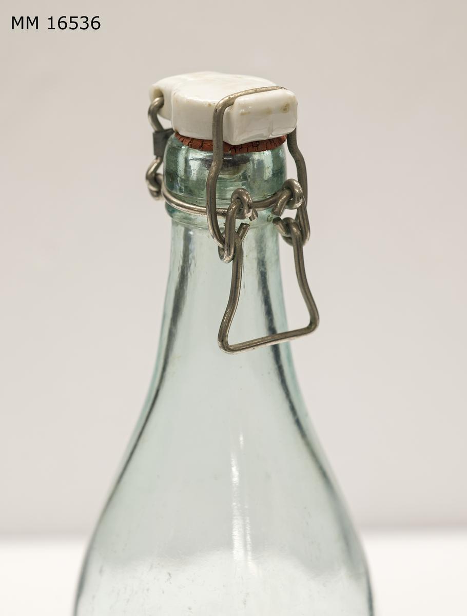 """Flaska av ljust glas. På kroppen är en etikett påklistrad med texten: """"Pärlo pärlande Kalifoniafrukter"""" """" inreg. varumärke FB"""" (ihopslingrade bokstäver i kronan av en blekingeek)  """"AB Förenade Bryggerierna Karlskrona"""". På vänstra kanten finns texten: """"Efter någon tids lagring avsätta sig en del av dryckens aromatiska ämnen. Flaskan vändes därför ett par gånger före öppnandet"""". Etikett är gjord i svart och rött på vit botten. I botten av flaskan finns i upphöjd relief: """"Årnäs 48"""". På flaskan sitter en kork. Denna sitter fäst om halsen och spänns över mynnningern med metallfäste. Själva korken är av porslin och mot mynningen sitter en gummiring."""