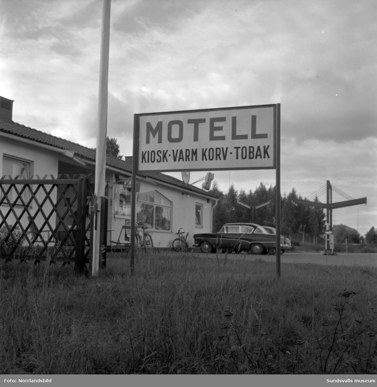 """Skyltning utefter vägen mellan Sundsvall och hälsingegränsen 1961. Bland annat Bergafjärden, Dingersjö, Bredsand och Kusten. I Njurundabommen fick länge trafikanterna söderifrån lätta på gasen och anamma ett makligare tempo. Men innan vägen som nu blivit """"gamla E4:an"""" byggdes, var det så här som korsningen i Bommen såg ut. Längst till höger i bild skymtar det före detta bankhuset som fortfarande finns kvar."""