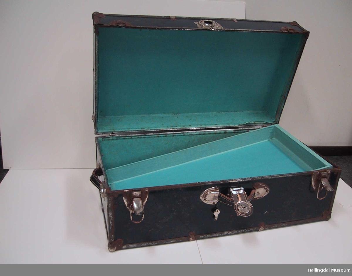 Kofferten har en innsats som hviler på fire punkt, to nøkler, metallbesklag langs alle kanter og i hjørnene.