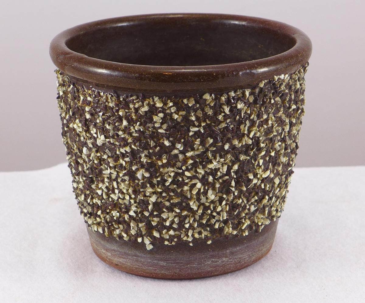 Potteskjular. Brunt leirgods. Glasur øvst på kant. Utvendig dekorert med noko som liknar småstein.