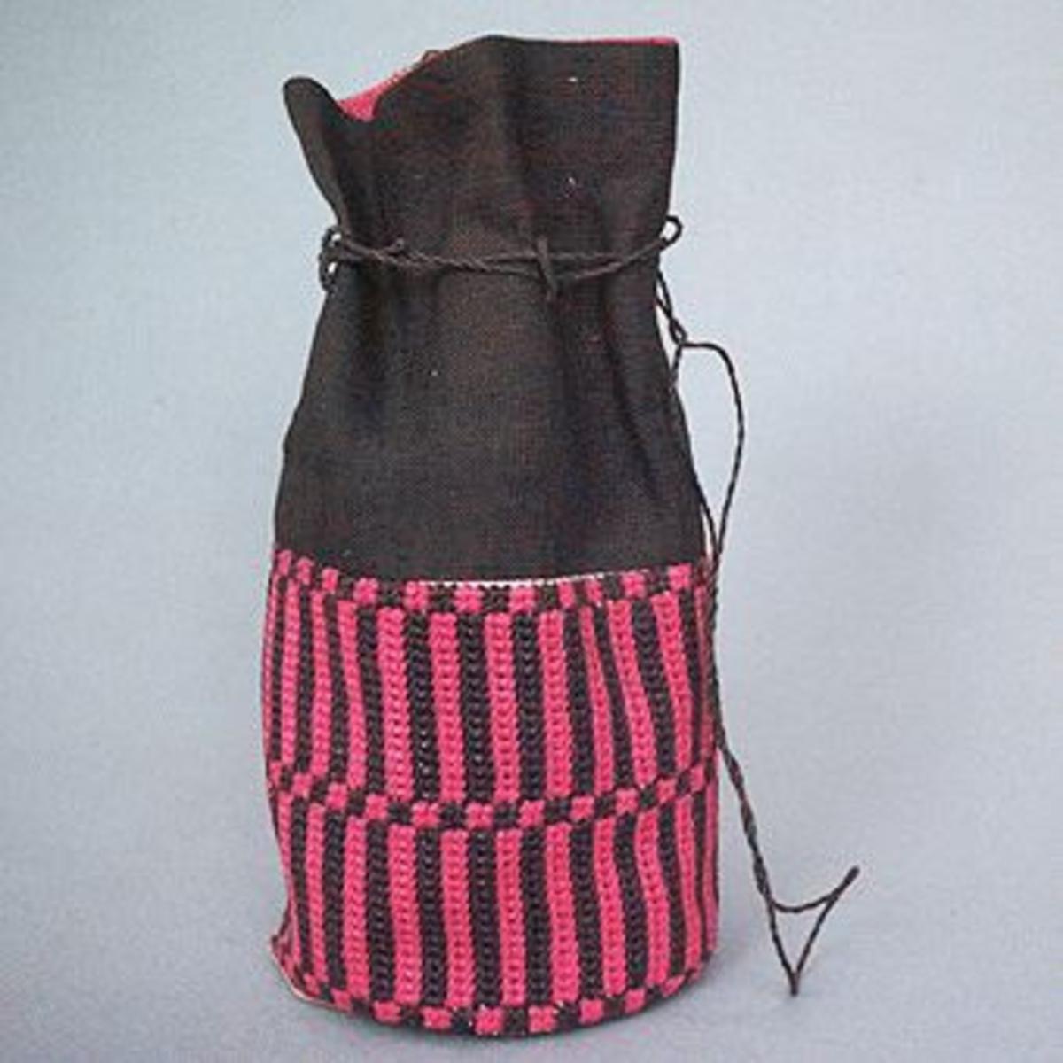 """Liten väska med nederdelen broderad med rosa och bruna ränder i tvistsöm och överdelen i brunt (obs, det är angivet grått linne på etiketten) linnetyg.På etikett fastsatt i botten på väskan anges materialåtgång och prisuppgift, texten är något svårläslig.""""Grått linne 15 x 35 cmSkollinne I vitt 10  x 35 cmRött linne till foder 23 x 35 cmGrått och rött linne till foder 15 x 15 cmHålsömsgarn 504 2 dHålsömsgarn 518 2 dPris färdig 30 kr, material 8,50 kr""""""""Modell får ej säljas""""Väskan har SHR:s pappersetikett från Kronobergs Läns Hemslöjdsförening Växjö, med påskrivet nummer: """"1411"""", fästad vid sig."""