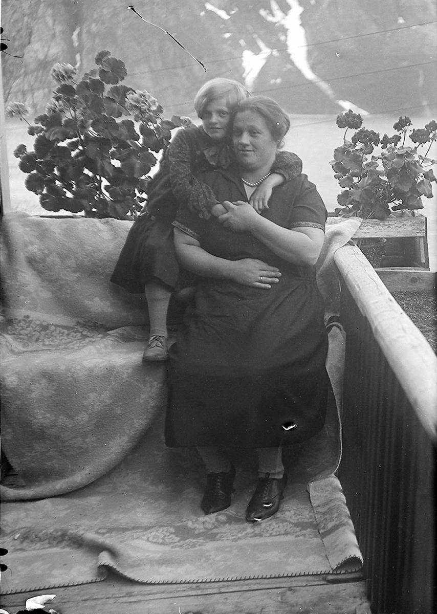 Portrett. Kvinne og jente. Sitter ute på en veranda. Jenta sitter bak kvinnen og holder om halsen hennes. Begge har kjole på seg.