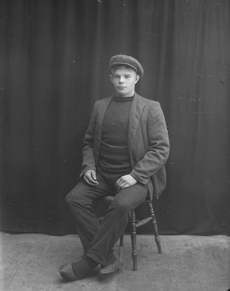 Portrett. Mann, sitter.Bildet er tatt på Reine i Lofoten.