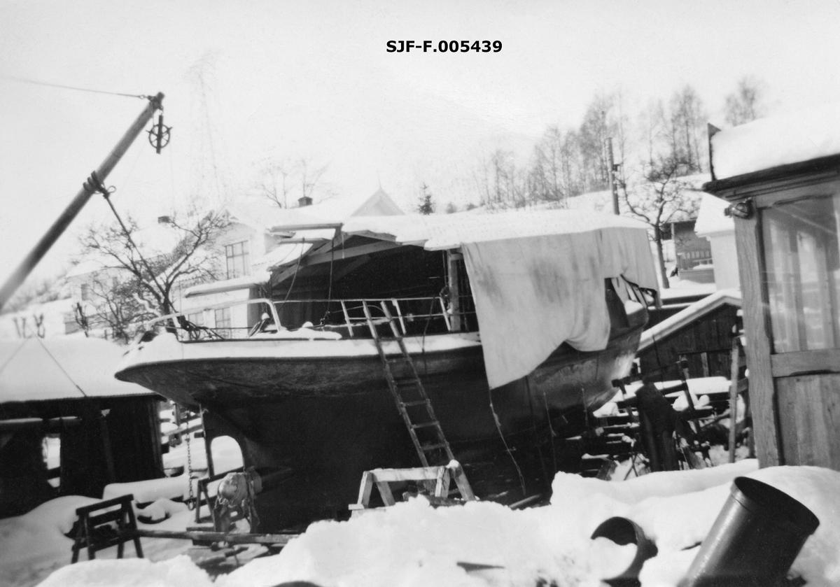Slepebåten «Axel», som tilhørte Skiensvassdragets Fellesfløtningsforening, fotografert på Knardalstrand slipp og verft i Porsgrunn vinteren 1953-54, da fartøyet ble ombygd fra damp- til dieseldrift.  Her ser vi båten i en fase da man hadde demontert styrhuset, åpnet dekket, for å få ut dampmaskinen ogdiselmotoren inn.  Derfor er den sentrale delen av dekket overbygd med et presenningtelt, som skulle hindre at det kom snø og annen fukt ned i båten.  Dieselmotoren tok atskillig mindre plass enn dampmaskinen hadde gjort.  Dette muliggjorde også betydelige ombyggingsarbeider under dekk, hvor det ble mer lugarplass og mer tidsmessige innredninger.  Styrhuset (til høyre i bildet) ble imidlertid heist på plass igjen og gjenbrukt.