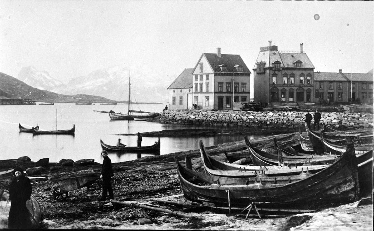 Tettsted - by. Havneområde med flere nordlandsbåter. Kaianlegg med brygge i bakgrunnen.