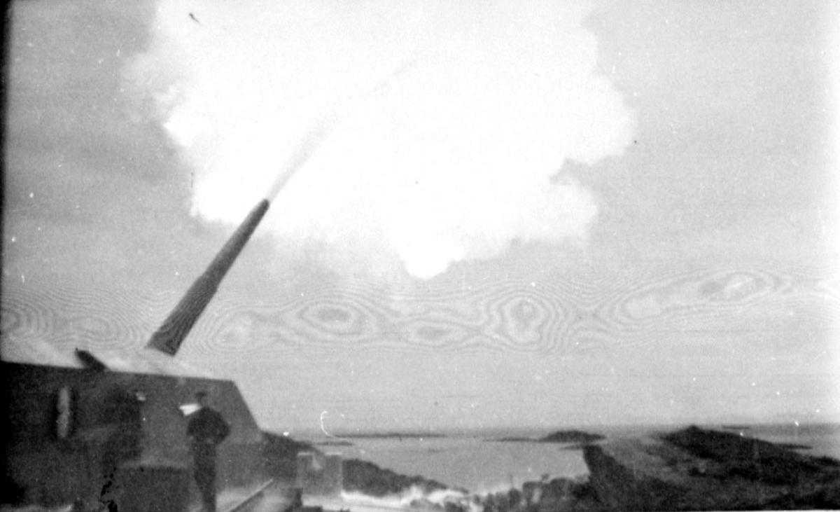 Militært anlegg, fesningsområde. Kanon avfyres. 1 person, mann i militæruniform ved kanonen.