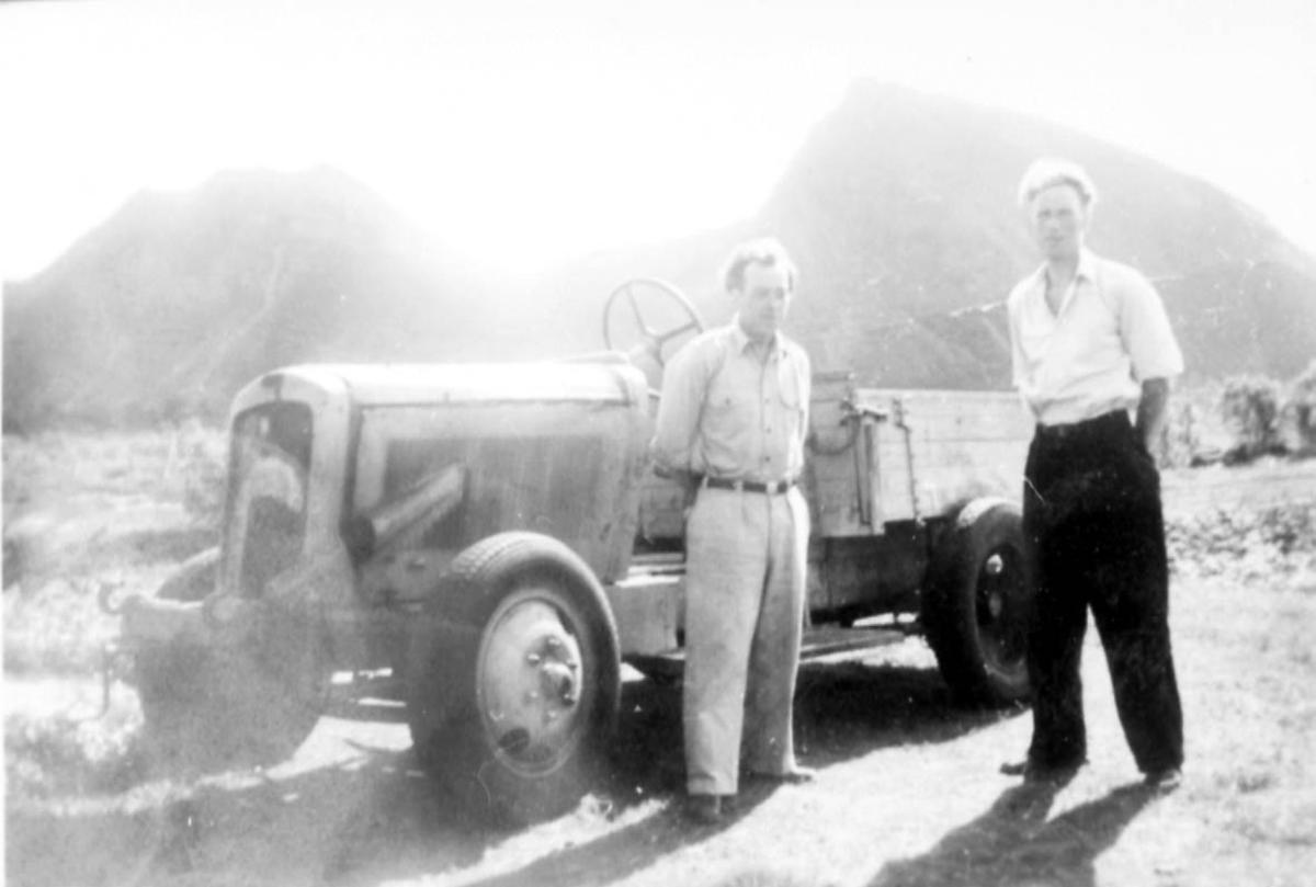 Jordbruk. 2 personer, menn ved en traktor.