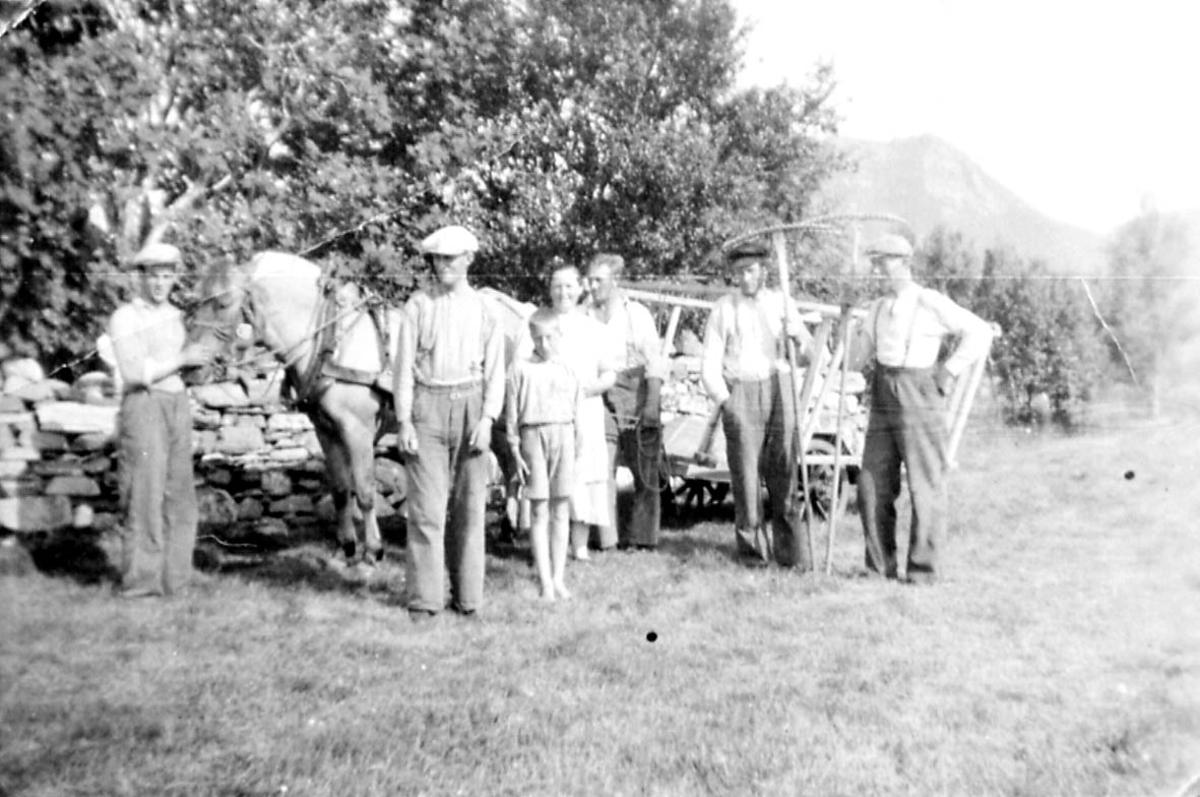 Jordbruk. Gruppebilde, kvinner menn og barn ved hest og høyvogn