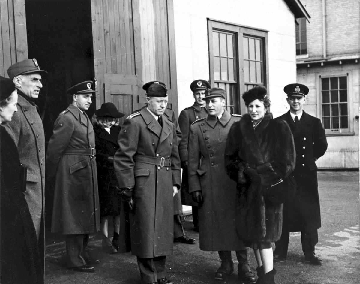 Gruppebilde. Flere personer, menn og kvinner. Mennene i militæruniformer. Utendørs. Kronprins Olav og kronprinsesse Märtha i midten.