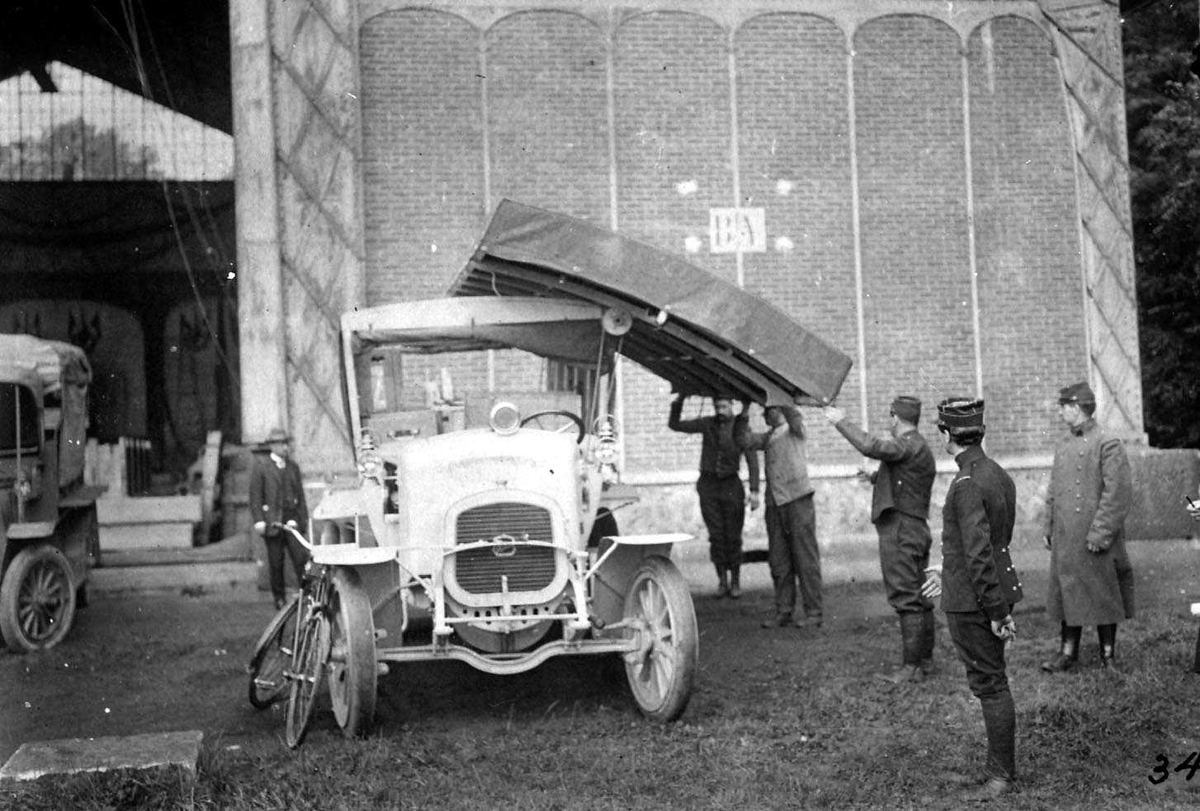 To kjøretøyer foran en hangar. Flyvinge på taket av det ene kjøretøyet. Flere personer, menn i militæruniform ved kjøretøyene.