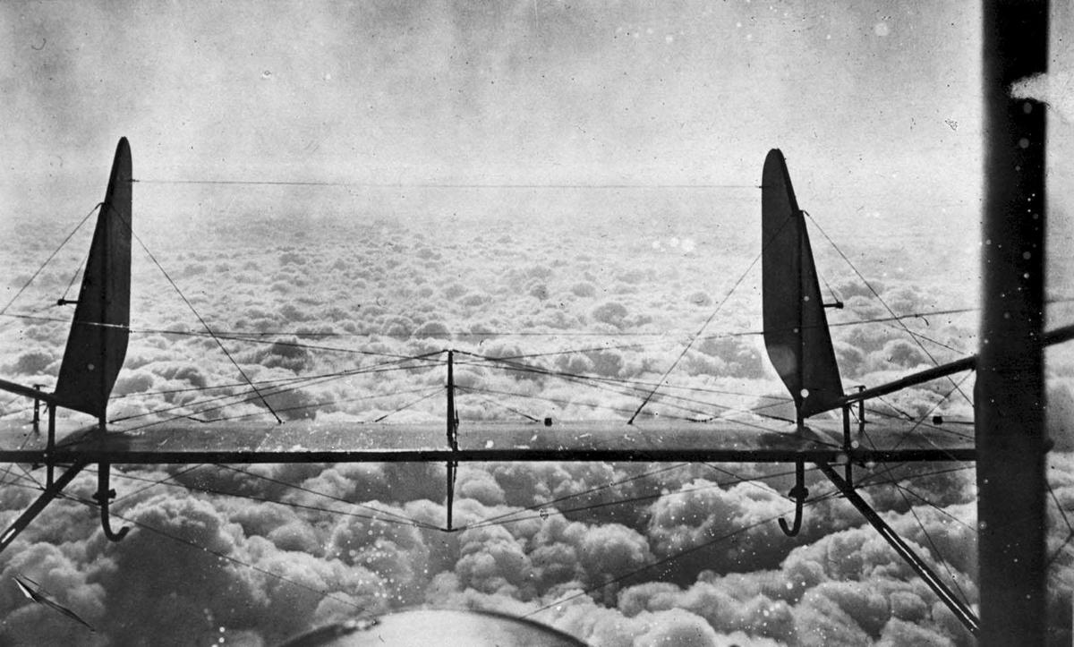 Luftfoto tatt fra fly. Haleroret til flyet i forgrunnen, skyer i bakgrunnen