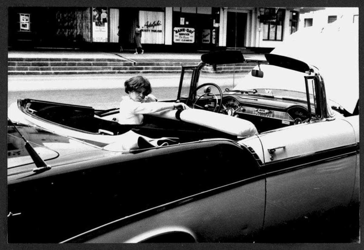 En person, kvinne, sitter i ett kjøretøy, personbil, en Chevrolet 1956 Bel Air.
