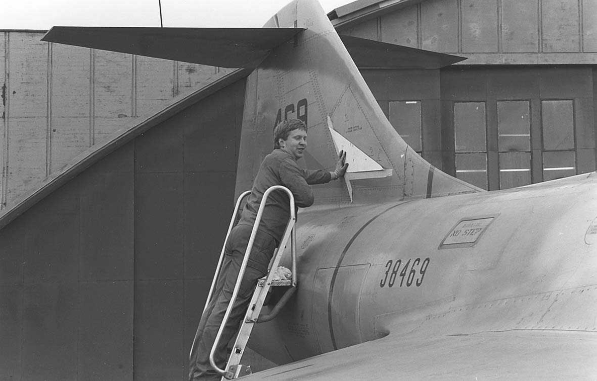 En person står i en stige som er satt opp mot haleroret på et fly.