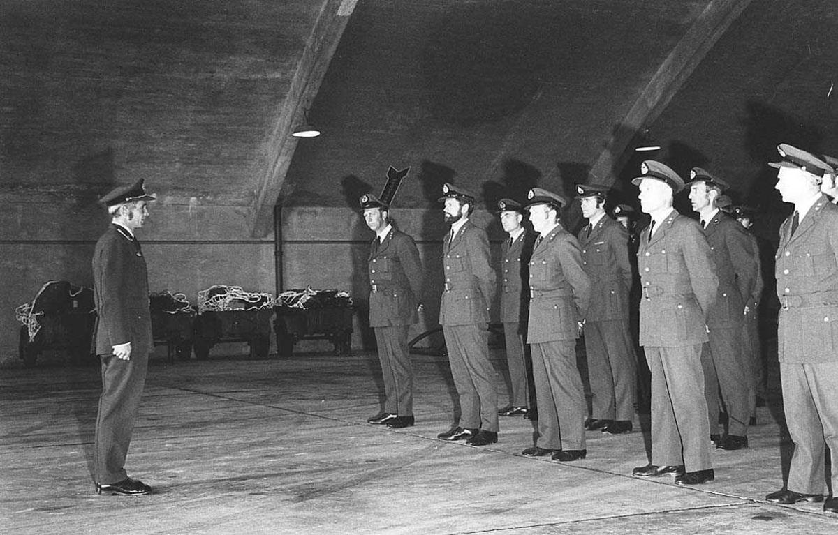 Personer på oppstilling i en hangar.