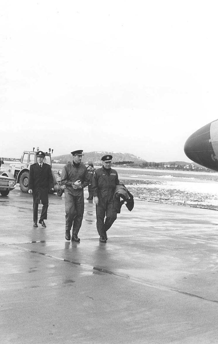 Kronprinsen spaserer med flere personer mot et fly.