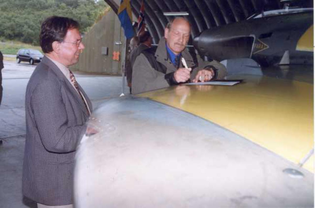 Lufthavn (flyplass). To personer, menn, undertegner en kontrakt/avtale på vingen til en SAAB J-32B Lansen , toseter.