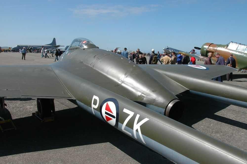 Lufthavn (flyplass). Ett fly på bakken. Jagerfly DH Vampire MK52, -. ZK-P  Flere personer i bakgrunnen.