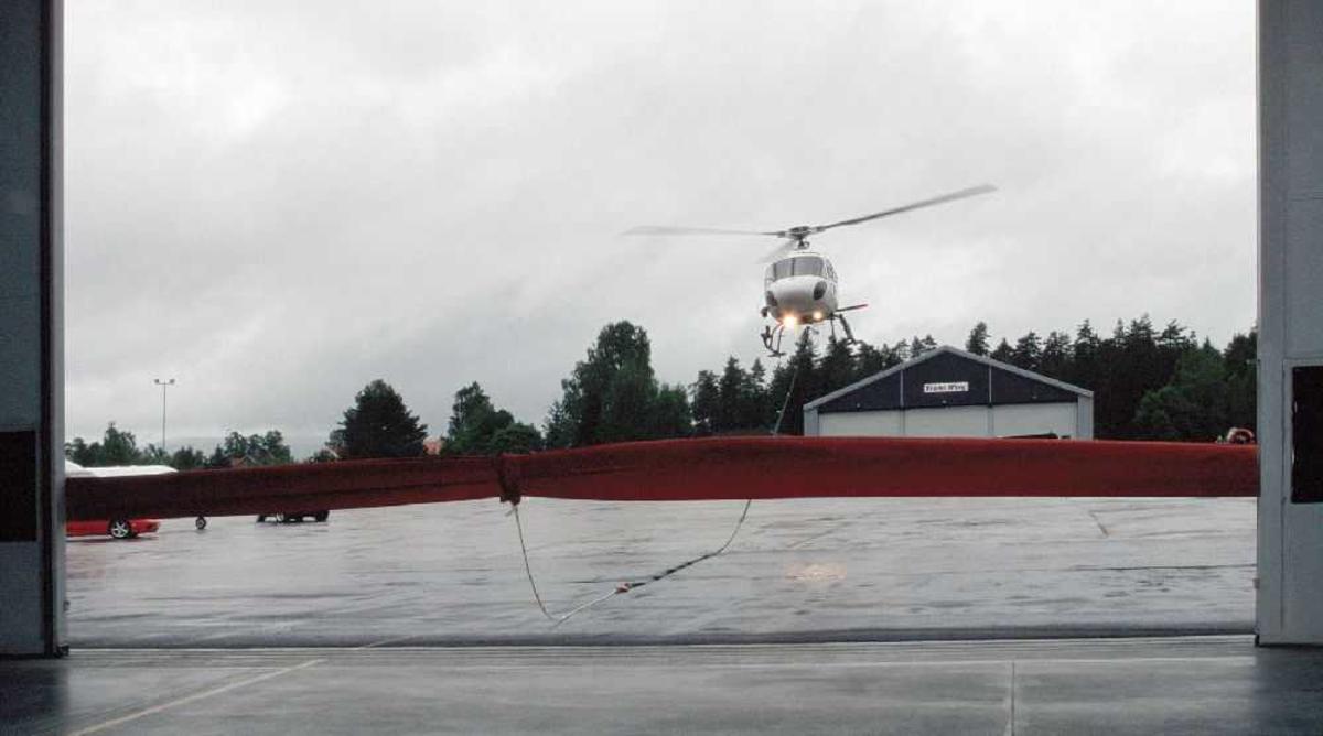 Lufthavn ()flyplass) Ett helikopter med utstyr (løft) like over bakken.