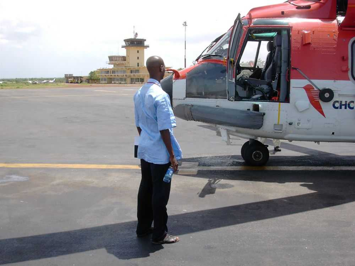 Lufthavn (flyplass). En person ved et helikopter. Super Puma, CHC Helicopters.