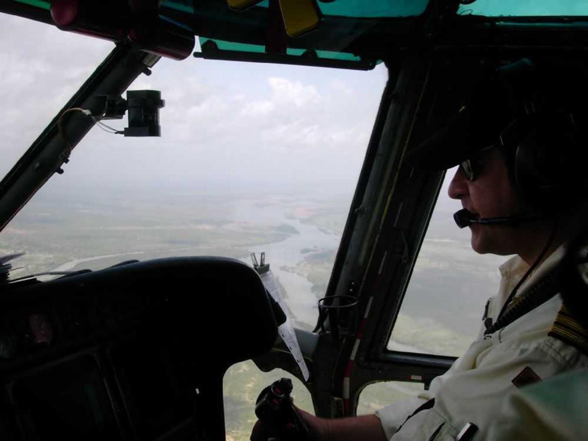 En person, flyger (pilot) inne i flycockpit.