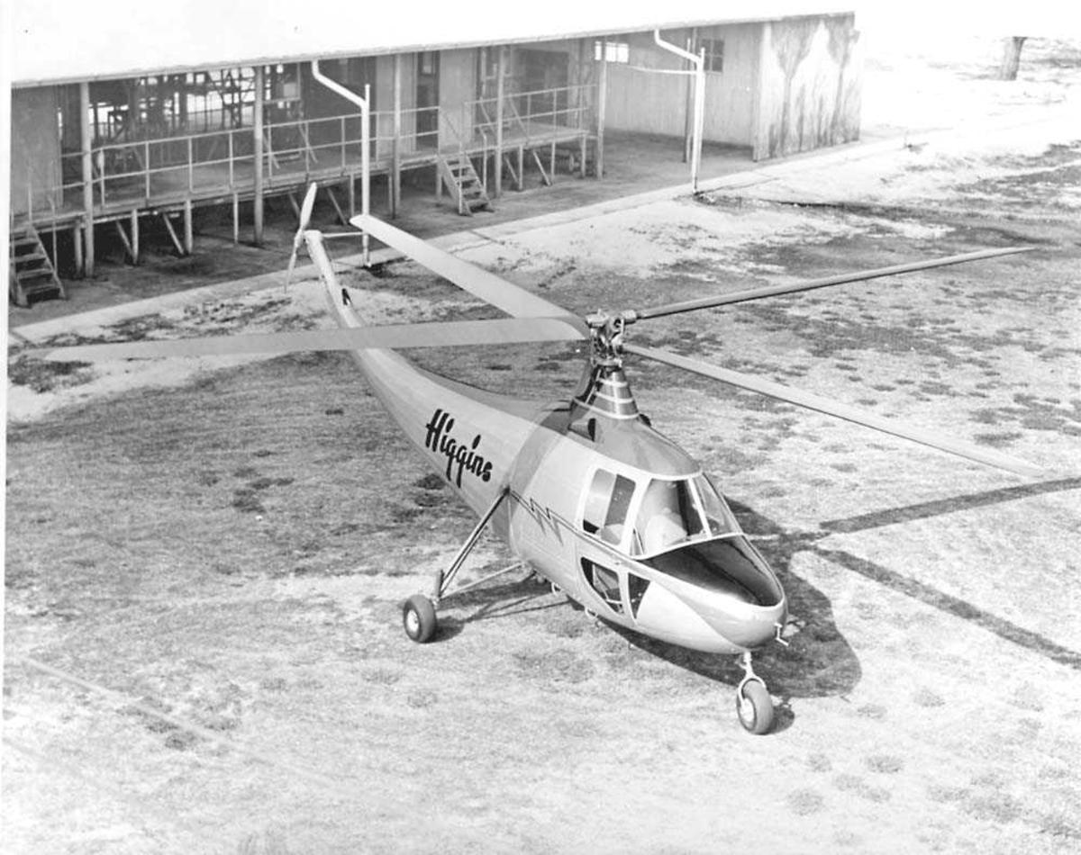 1 helikopter på bakken. Higgins. Bygning i bakgrunnen.