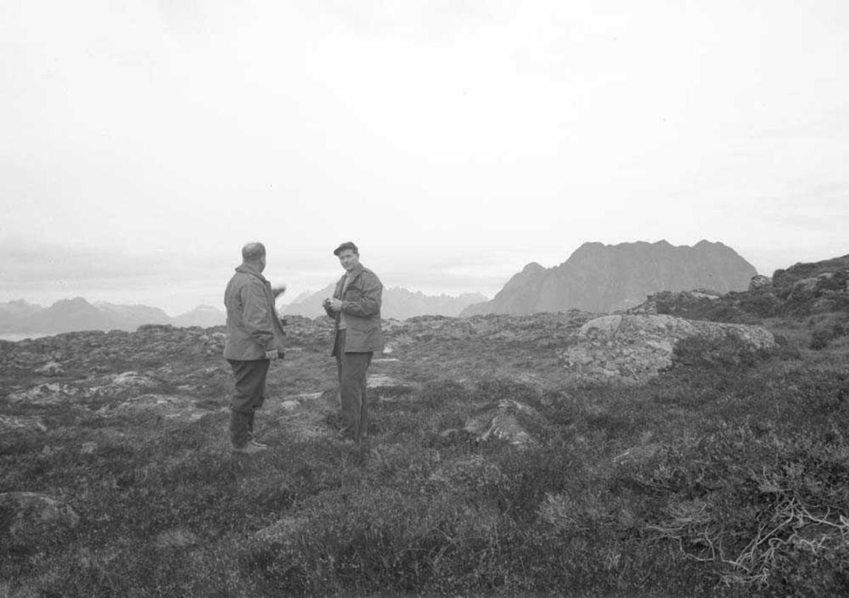 To personer, menn på et fjell. Taubaneanlegg på Skrova.