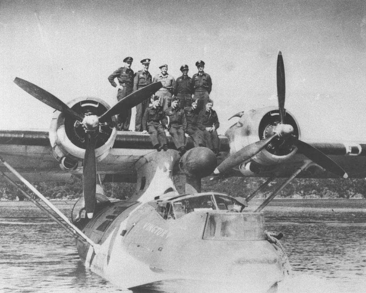 Gruppefoto av mannskapet på Catalina. Bildet er tatt høyst sannsynlig rett etter 2. verdenskrig fordi det norske flagget er malt på flyet, og det ble gjort rett etter krigen. Flyet heter Vingtor V. Kronprins Olav står i midten.