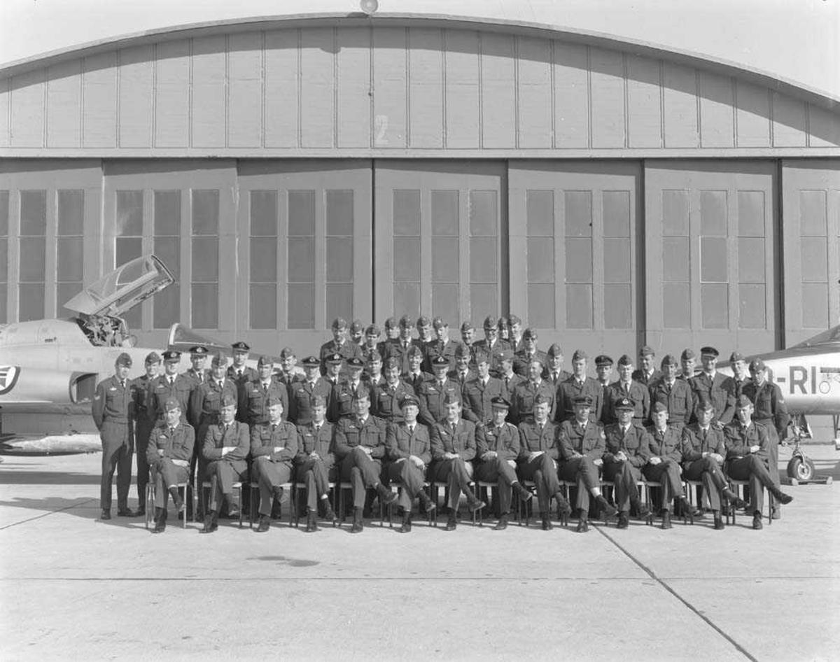 Gruppefoto av personellet ved 334 skvadron, Bodø flystasjon. Bak sees 2 stk F-5 Freedom Fightere. Gruppen er oppstilt foran Hangar 2 på 334 skvadrons området.