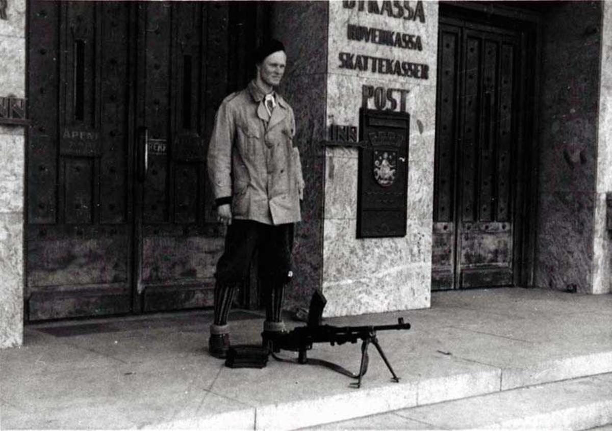 En person som står vakt utenfor en bygning. Mann. Et våpen står foran han.
