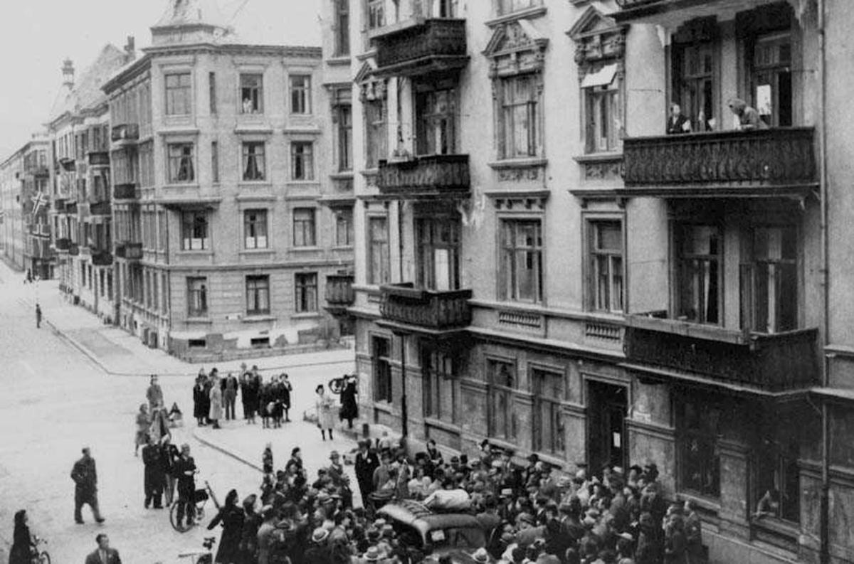 Folkemengde samlet rundet en bil som står parkert. Noen personer på balkonger i bygningen bak. Bygninger med norsk flagg i bakgrunnen.