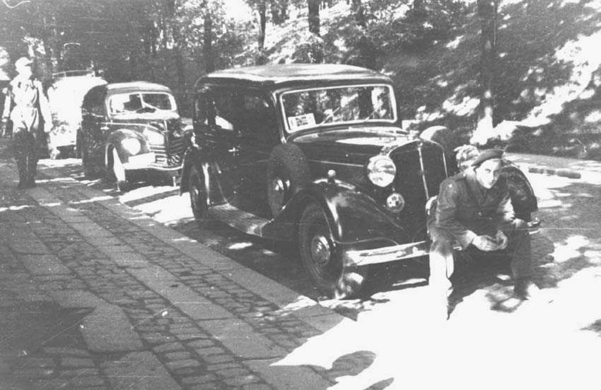 En person. Mann. Sitter foran en bil.. Biler og en person i bakgrunnen.