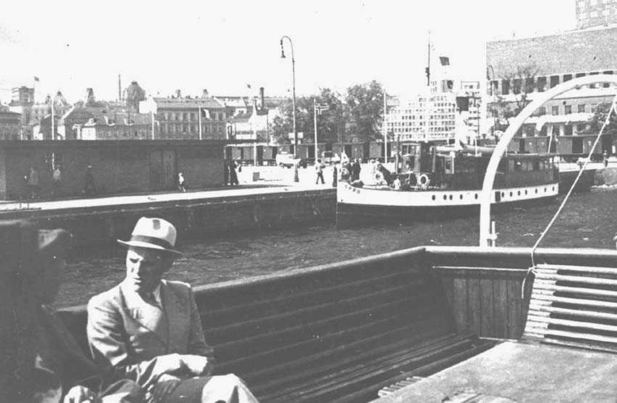Utsikt over kaiomerådet ved rådhuset. To personer sitter på en benk. En båt ligger til kai. Litt av rådhuset til høyre. Bygninger i bakgrunnen.