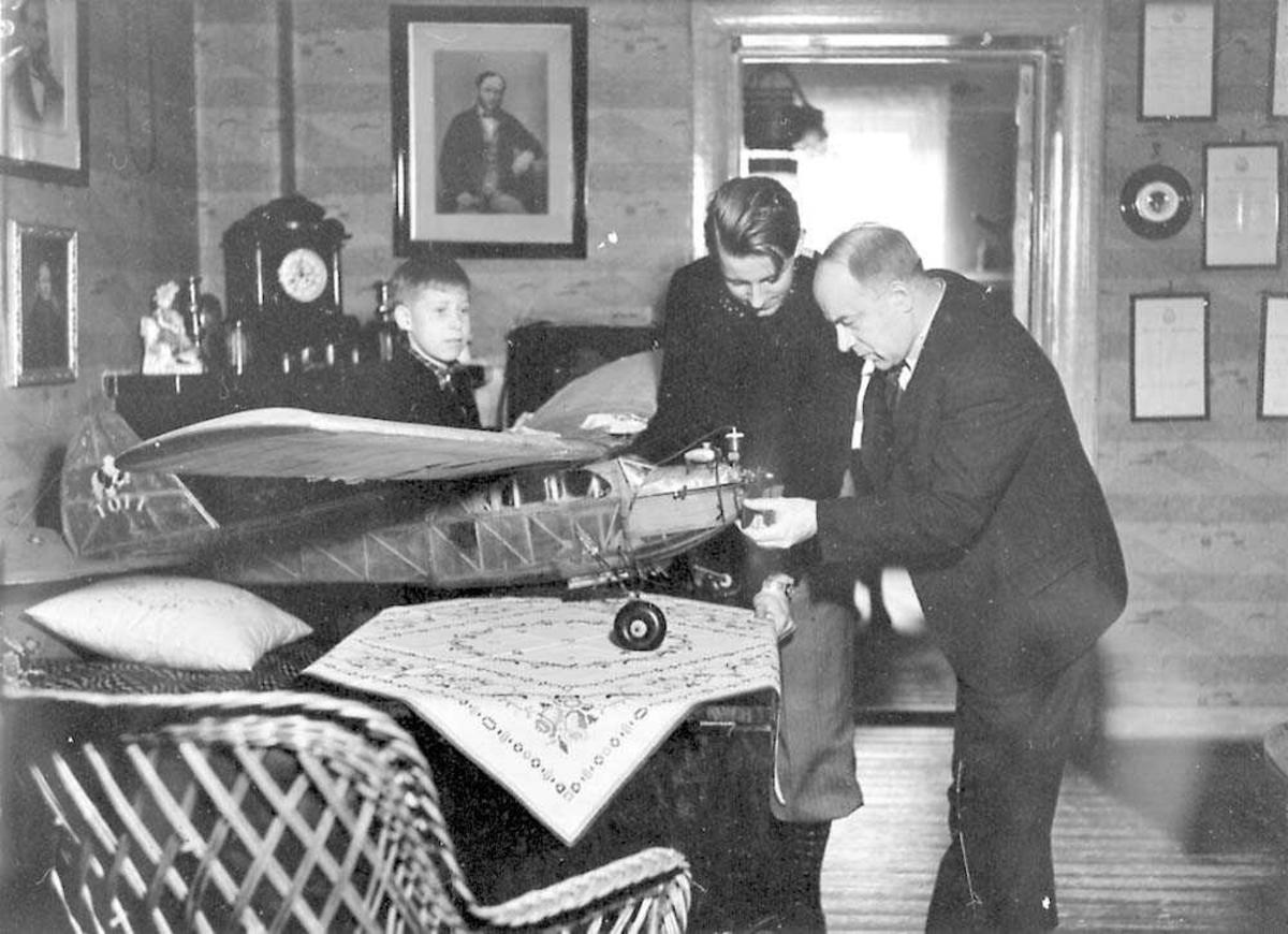 Tre personer, to voksne og et barn, samlet rundt et modellfly. Modellflyet står på et bord. Bildet tatt innendørs.