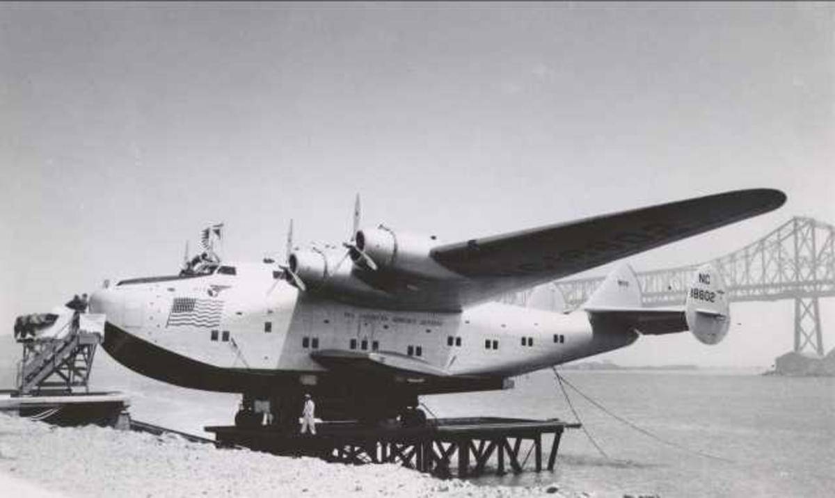 """Ett fly på bakken. Boeing 314 Clipper. NC 18602 """"California Clipper"""". Noen personer ved flyet. Bro ses t.h. bak."""