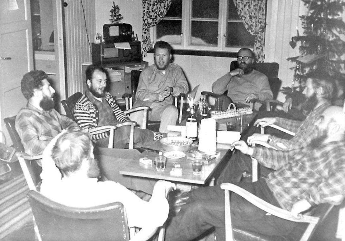 Flere personer som sitter rundt et bord. Juletre i bakgrunnen.