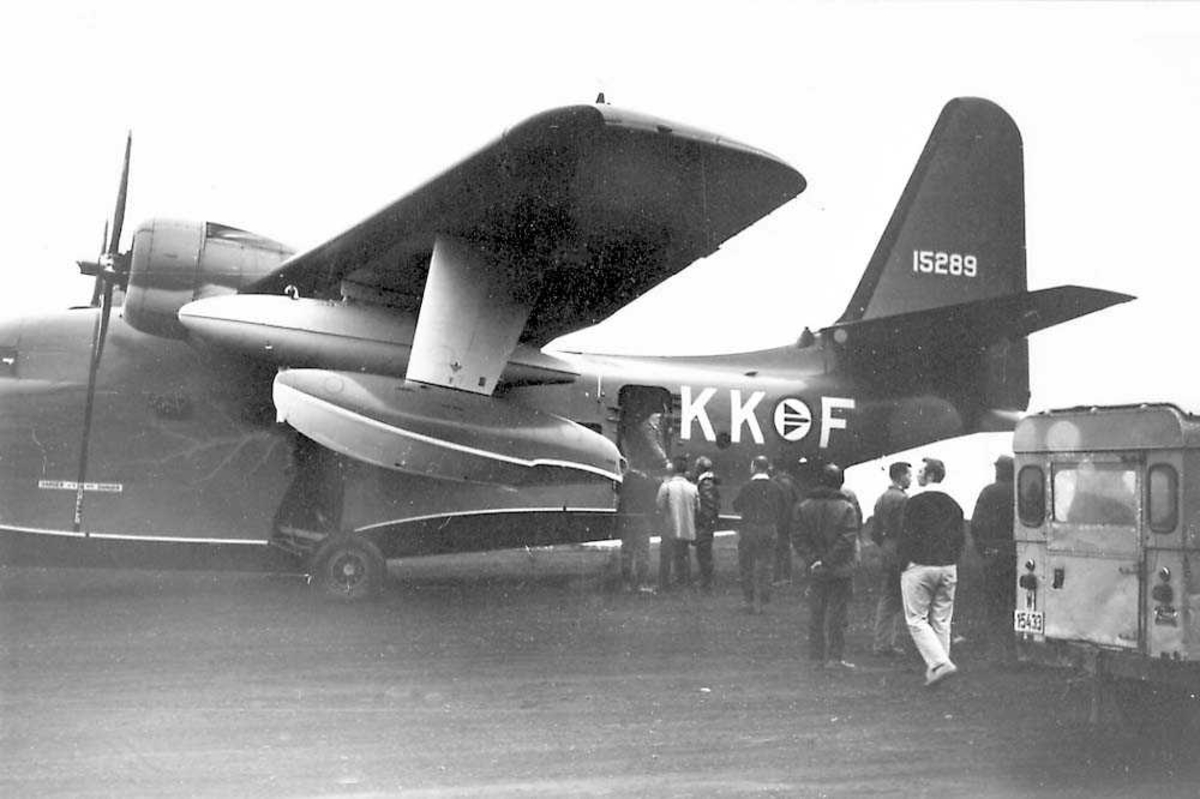 "Et fly på bakken. ""Albatros"" SA16B. Flere personer foran flyet."