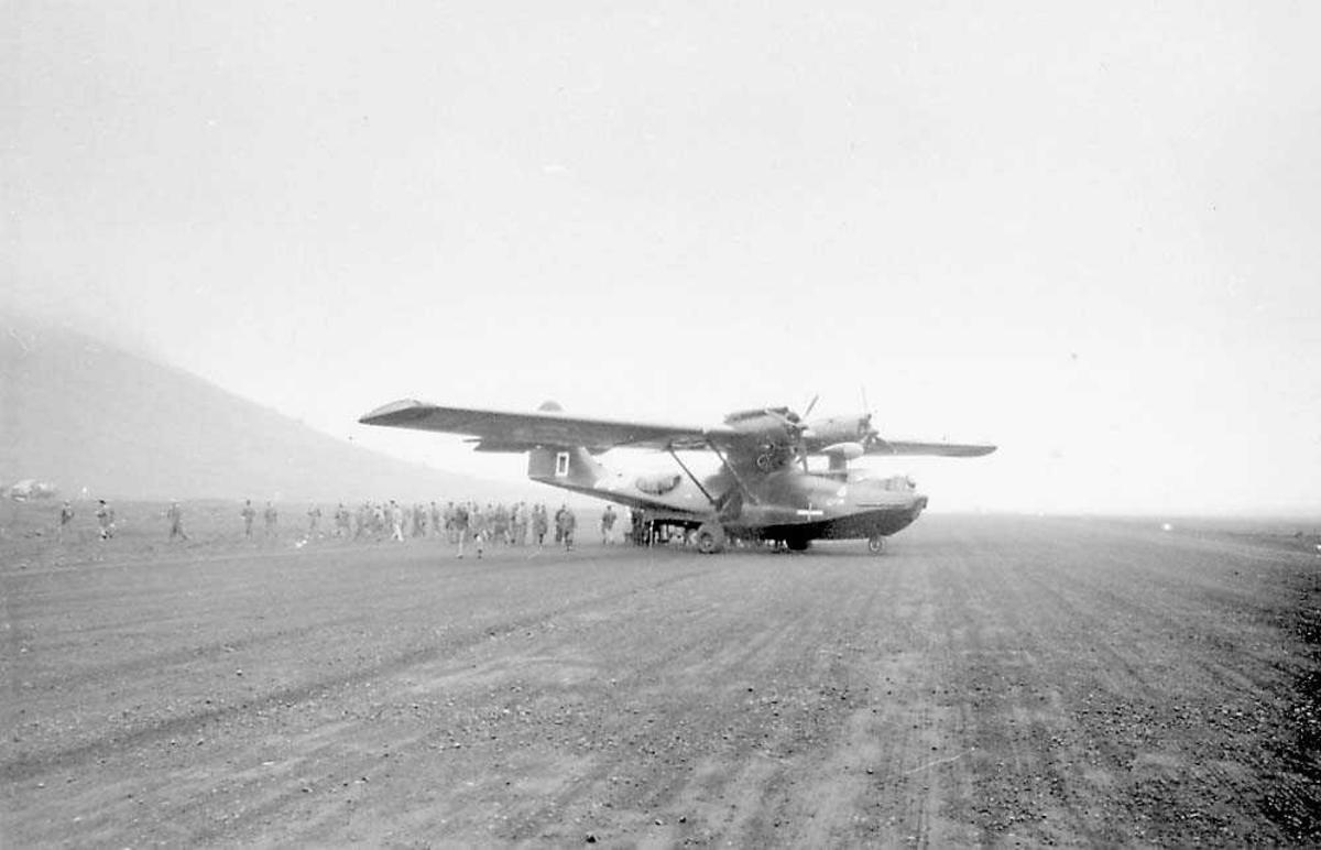 Et fly på bakken. Catalina. Flere personer bakom flyet.
