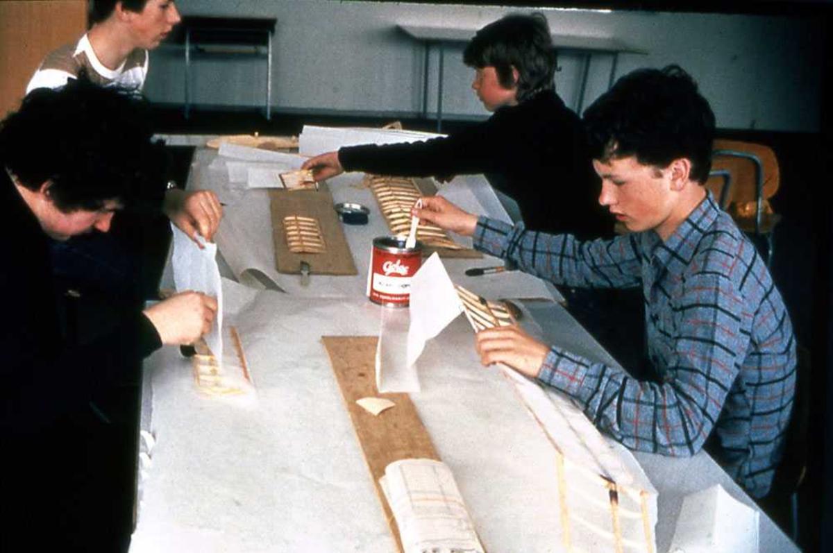 Fire gutter ved langbord. Modellflybygging.